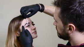 Το Beautician, ειδικός της μόνιμης σύνθεσης εφαρμόζει το τοπικό αναισθητικό πριν από τη μόνιμη διαδικασία makeup brow μέσα απόθεμα βίντεο
