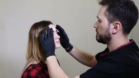 Το Beautician, ειδικός της μόνιμης σύνθεσης εφαρμόζει το τοπικό αναισθητικό πριν από τη μόνιμη διαδικασία makeup brow μέσα φιλμ μικρού μήκους