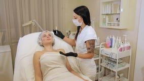 Το Beautician επισύρει την προσοχή τα περιγράμματα ενός άσπρου μολυβιού στο πρόσωπο του ασθενή απόθεμα βίντεο