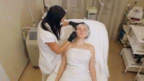 Το Beautician επισύρει την προσοχή τα περιγράμματα ενός άσπρου μολυβιού στο πρόσωπο του ασθενή φιλμ μικρού μήκους