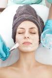 Το Beautician εφαρμόζει τη μάσκα προσώπου με τη βούρτσα στην όμορφη νέα γυναίκα στο σαλόνι SPA καλλυντική φροντίδα δέρματος διαδι στοκ φωτογραφία