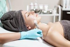 Το Beautician εφαρμόζει τη μάσκα προσώπου με τη βούρτσα στην όμορφη νέα γυναίκα στο σαλόνι SPA καλλυντική φροντίδα δέρματος διαδι στοκ φωτογραφία με δικαίωμα ελεύθερης χρήσης