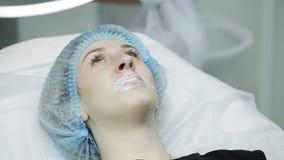 Το Beautician κάνει την έγχυση τα πλαστικά χείλια Νέα γυναίκα στη χειλική αύξηση σε μια κλινική φιλμ μικρού μήκους