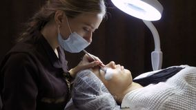 Το Beautician κάνει τη διαδικασία της επέκτασης eyelash στο σαλόνι ομορφιάς απόθεμα βίντεο