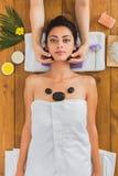Το Beautician κάνει stone massage spa για τη γυναίκα στο κέντρο wellness Στοκ Φωτογραφίες