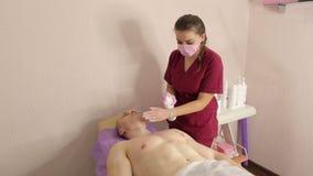 Το beautician μεταχειρίζεται το δέρμα ενός ατόμου μετά από depilation του γλυκασμού στηθών απόθεμα βίντεο