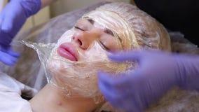 Το beautician προετοιμάζει το αναισθητικό κρέμας κοριτσιών προσώπου πριν από την ομορφιά φιλμ μικρού μήκους