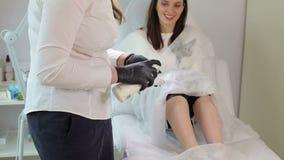 Το Beautician προετοιμάζει το πόδι γυναικών ` s για depilation φιλμ μικρού μήκους