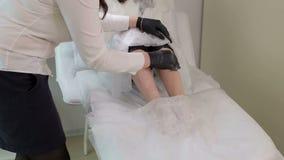 Το Beautician προετοιμάζει τα πόδια γυναικών ` s για depilation φιλμ μικρού μήκους