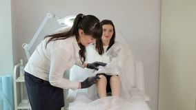 Το Beautician προετοιμάζει τα πόδια γυναικών ` s για depilation απόθεμα βίντεο