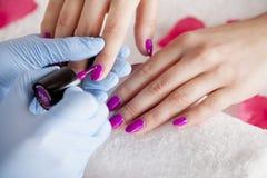 Το beautician χρωματίζει τα καρφιά Στοκ Εικόνες