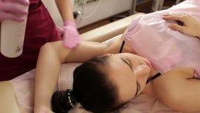Το Beautician ψεκάζει την απολυμαντική λύση στις μασχάλες πριν από depilation απόθεμα βίντεο
