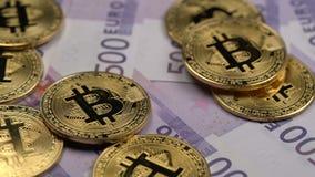 Το Bitcoin, το cryptocurrency, τα χρυσά bitcoins και τα πραγματικά χρήματα πεντακόσια ευρώ περιστρέφονται στην περιστροφική πλάκα απόθεμα βίντεο