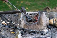 Το Blacksmithing, ένα red-hot κομμάτι του σιδήρου σφυρηλατεί το φούρνο Στοκ εικόνα με δικαίωμα ελεύθερης χρήσης