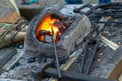 Το Blacksmithing, ένα red-hot κομμάτι του σιδήρου σφυρηλατεί το φούρνο Στοκ Εικόνα