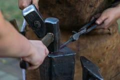 Το Blacksmithing, δύο σιδηρουργοί χτύπησε το αμόνι με ένα σφυρί Στοκ Εικόνες