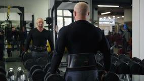 Το Bodybuilder παίρνει τους βαριούς αλτήρες, εξετάζει τον στον καθρέφτη, κάνει την άσκηση 4K η αργή Mo φιλμ μικρού μήκους