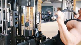 Το Bodybuilder σε μια μαύρη κορυφή δεξαμενών εκτελεί μια άσκηση στο τράβηγμα ώμων κάτω από τις μηχανές φιλμ μικρού μήκους
