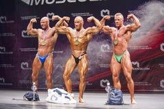 Το Bodybuilders παρουσιάζει τη διάπλασή τους και τα μετάλλια και τρόπαιά τους Στοκ εικόνες με δικαίωμα ελεύθερης χρήσης