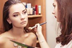 Το Brunette αποτελεί τη γυναίκα καλλιτεχνών ισχύουσα να αποζημιώσει ένα BR brunette Στοκ εικόνες με δικαίωμα ελεύθερης χρήσης