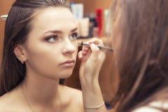 Το Brunette αποτελεί τη γυναίκα καλλιτεχνών ισχύουσα να αποζημιώσει ένα BR brunette Στοκ Εικόνα