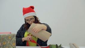 Το brunette γοητείας δένει την κόκκινη κορδέλλα γύρω από το δώρο απόθεμα βίντεο