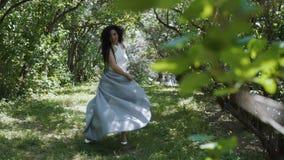 Το brunette γοητείας κινεί το μακρύ φόρεμά της που στέκεται σε έναν πράσινο κήπο φιλμ μικρού μήκους