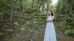 Το brunette κοριτσιών σε ένα μπλε φόρεμα με τα λουλούδια στα χέρια της στέκεται στα ξύλα και θαυμάζει τη φύση απόθεμα βίντεο