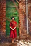 Το brunette κοριτσιών στο κόκκινο εκλεκτής ποιότητας φόρεμα στέκεται κοντά στις παλαιές πόρτες Στοκ Εικόνες