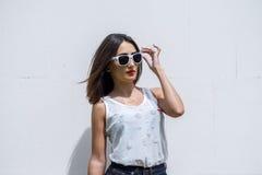 Το brunette κοριτσιών το καλοκαίρι στο πάρκο με τη στήριξη μιας άσπρης μπλούζας στον τρόπο ζωής μόδας υποβάθρου, εξευγενίζει το β Στοκ εικόνες με δικαίωμα ελεύθερης χρήσης