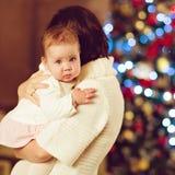 Το brunette μητέρων αγκαλιάζει λίγο χαριτωμένο chubby κοριτσάκι σε ένα λευκό Στοκ Εικόνα