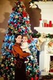 Το brunette μητέρων αγκαλιάζει λίγο χαριτωμένο chubby κοριτσάκι σε ένα λευκό Στοκ Εικόνες