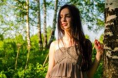 Το Brunette στέκεται κοντά στη σημύδα στο δάσος Στοκ εικόνα με δικαίωμα ελεύθερης χρήσης