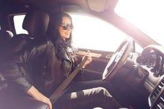 Το Brunette στη γυναίκα γυαλιών ηλίου στερεώνει το ακριβό αυτοκίνητο Στοκ Εικόνες