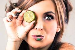 Το brunette Headshot, σκοτεινή αίγλη κοιτάζει και πράσινο κραγιόν, που καλύπτει ένα μάτι με τον ανοικτό ασβέστη, εξετάζοντας τη κ Στοκ Εικόνα