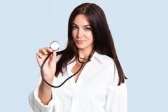 Το brunette Taleneted που ο νέος θηλυκός γιατρός ή ο παιδίατρος στο άσπρο παλτό, κρατά phonendoscope, θεραπεύει τα μικρά παιδιά,  στοκ φωτογραφία