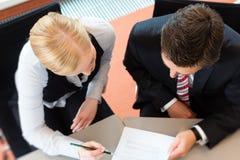 Το Businesspeople κάθεται στο γραφείο γραφείων Στοκ εικόνα με δικαίωμα ελεύθερης χρήσης