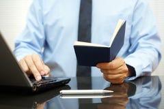 Το Bussinessman διαβάζει τα informations από το σημειωματάριο και δακτυλογραφεί επάνω Στοκ Εικόνες