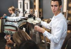 Το Caffe Italiano στο ιταλικό barista σερβιτόρων ΦΡΑΓΜΩΝ εξυπηρετεί τη γιγαντιαία καφετιέρα moka καφέ Στοκ Φωτογραφίες
