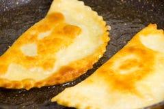 Το Chebureks ψήνεται καυτό κατακόκκινο τριζάτο σε έναν νόστιμο skillet στοκ εικόνα