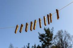 Το Clothespins για τα ενδύματα και τα ενδύματα κρεμούν ενάντια στο μπλε ουρανό μια ηλιόλουστη ημέρα σε ένα στενό στοκ εικόνες