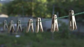 Το Clothespins κρεμά σε ένα σχοινί στο υπαίθριο θερινό σπίτι φιλμ μικρού μήκους