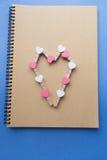 Το Clothespins με τις καρδιές είναι σημειωματάριο Μπλε έγγραφο ανασκόπησης Στοκ φωτογραφίες με δικαίωμα ελεύθερης χρήσης