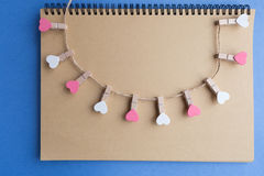 Το Clothespins με τις καρδιές είναι σημειωματάριο Μπλε έγγραφο ανασκόπησης Στοκ Φωτογραφία