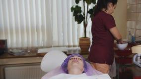 Το Cosmetician σκουπίζει το πρόσωπο του θηλυκού ασθενή με έναν οφθαλμό βαμβακιού πριν από τη διαδικασία, απολύμανση απόθεμα βίντεο