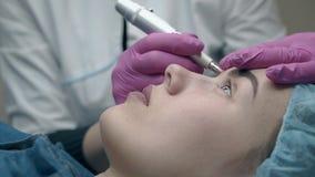Το Cosmetician στα αποστειρωμένα γάντια εφαρμόζει τη δερματοστιξία φρυδιών αργή φιλμ μικρού μήκους