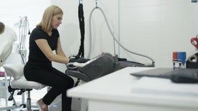 Το Cosmetologist ανοίγει τον ειδικό ιατρικό εξοπλισμό πριν από τη διαδικασία στο κέντρο ομορφιάς, σε αργή κίνηση φιλμ μικρού μήκους