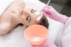 Το Cosmetologist εφαρμόζει την του προσώπου κρέμα Στοκ φωτογραφία με δικαίωμα ελεύθερης χρήσης