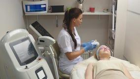 Το Cosmetologist εφαρμόζει το πήκτωμα στο πρόσωπο του ασθενή πριν από τη διαδικασία απόθεμα βίντεο