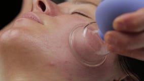 Το Cosmetologist κάνει το μασάζ αντι-γήρανσης με τις κενές τράπεζες κενό μασάζ προσώπου για την αναγέννηση δερμάτων απόθεμα βίντεο
